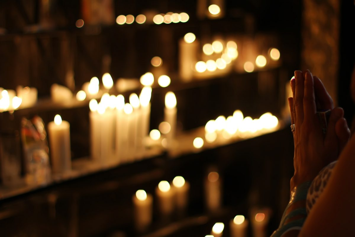 close-up-photograph-of-person-praying-in-front-lined-candles-1024900-1200x800.jpg